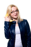 Girl in glasses tries to speak by means of a banana Stock Photos