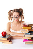 Girl in glasses on white background sitting at table with books Royalty Free Stock Photo
