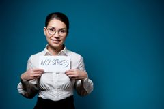 Girl with glasses and a white shirt with a fake smile holds a piece of paper with the words no stress
