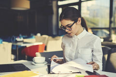 Girl in glasses working. Skilled professional female administrative manager of coffee shop checking documentation for month before sending report to financier Stock Photos
