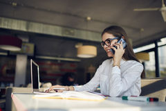 Girl in glasses working telephone conversation sitting in food court using technology Stock Photos