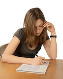 The girl in glasses writes to writing-books Royalty Free Stock Photo