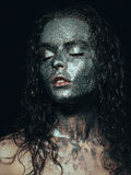 Girl in glitter. On her face with wet curly hair on black background Close-up Royalty Free Stock Image