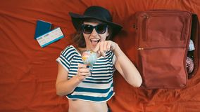 Girl with Globe on Bed. Cheerful girl in black hat and dark blue sunglasses turning the globe while lying on the bed stock footage