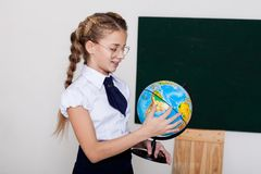 Girl with a globe at the Blackboard in a class lesson stock images