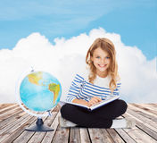 Girl with globe and book Stock Photography