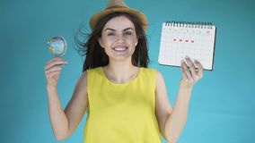 Girl with globe and calendar. Smiling pretty woman in cute sunhat looking at the globe and then at calendar, anticipating upcoming holidays, isolated slowmotion stock video footage