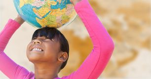 Girl with globe on head against blurry brown map Stock Image