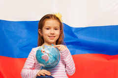 Girl with globe in her hand against flag of Russia stock photography