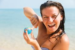 Girl with a globe in his hand. Closeup. Laughing girl on ocean background shows finger on small globe Stock Photo