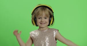 Girl in glossy dress and headphone listening to music and dancing. Chroma Key. Girl in glossy dress and headphone listening to music and dancing. Happy four stock footage