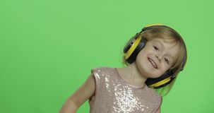 Girl in glossy dress and headphone listening to music and dancing. Chroma Key. Girl in glossy dress and headphone listening to music and dancing. Happy four stock video