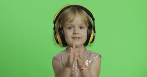 Girl in glossy dress and headphone listening to music and dancing. Chroma Key. Girl in glossy dress and headphone listening to music and dancing. Happy four stock video footage