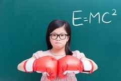 Girl with glove and e=mc2. Cute girl with glove and e=mc2 on green chalkboard Royalty Free Stock Images