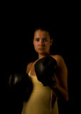 Girl in gloves. Girl in black boxing gloves on black background Royalty Free Stock Photography