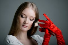 Girl in gloves with brush Stock Photo