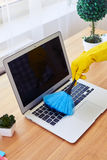 Girl in gloves dusting with small broom keyboard Royalty Free Stock Image