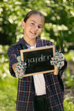 Girl in gloves holding blackboard with text Stock Image