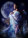 Girl in the glow of the moon. Half-naked girl wrapped in translucent white cloth moves in the light of the full moon royalty free stock photography