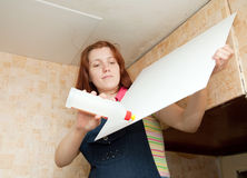 Girl glues ceiling tile Royalty Free Stock Images