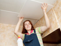 Girl glues ceiling tile Stock Image