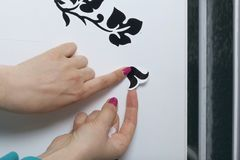 The girl glues the cut out elements from self-adhesive paper, to mask the defects of the white door. Stock Image