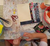 A girl glues and cuts fabric into a picture Royalty Free Stock Photo