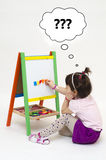 Girl glues magnetic letters on white board wondering. Isolated on white background Royalty Free Stock Photo