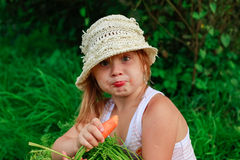 Girl gnaws carrot Royalty Free Stock Photo