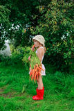 Girl gnaws carrot with a bunch of carrots Stock Photo