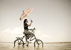 Girl go for a cycle ride at water. With umbrella in hand. Photo in retro style Royalty Free Stock Images