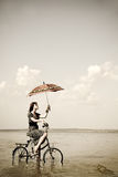 Girl go for a cycle ride at water with umbrella. In hand. Photo in retro style Stock Photos