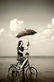 Girl go for a cycle ride at water with umbrella. In hand. Photo in retro style Stock Photo