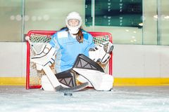 Girl goaltender crouches in crease to protect net. Female goaltender crouches in the crease to protect the net against puck stock image