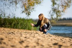 Girl walking along the beach. Girl goes along the beach in the autumn day royalty free stock image