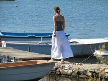Girl goes along the beach on a Sunny day. ahead of the wooden bridge to which the boats are tied.  stock image