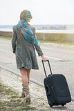 Girl goes along the road by the sea with a suitcase Stock Photography