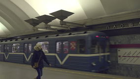 Girl goes along the subway platform. And subway train departs from the station in the background stock footage