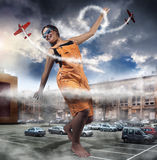 Girl goes around the city. Giant girl goes through the city in an orange jumpsuit Royalty Free Stock Images