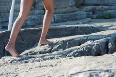 The girl goes barefoot on the rocks, climbing up royalty free stock photo