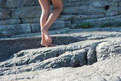 The girl goes barefoot on the rocks, climbing up stock photos