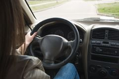 The girl goes behind the wheel of a car, hands on the steering wheel. Driving a large car stock images