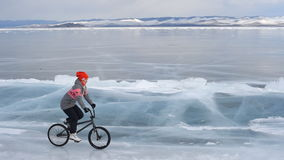 The girl goes on a bmx on ice. The girl goes on a bmx on Lake Baikal ice stock video footage