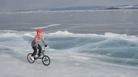 The girl goes on a bmx on ice. The girl goes on a bmx on Lake Baikal ice stock video