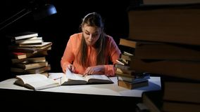 Girl goes through the book and find the right information. Black background stock video footage