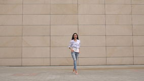 Girl goes on camera on background white wall. stock video footage