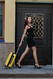 Girl goes and carries a suitcase on wheels. Royalty Free Stock Image