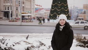 Girl goes on a city of Christmas tree. Cheerful girl on a street decorated for Christmas stock video footage