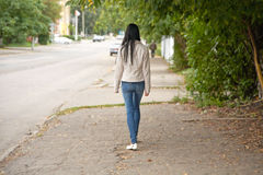 Girl goes on city street in the autumn afternoon Stock Images
