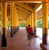 Girl goes deep into the palace between gold columns Royalty Free Stock Photo
